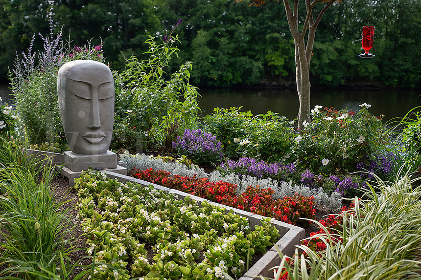 Home flower garden in full bloom with Bhudda sculpture.