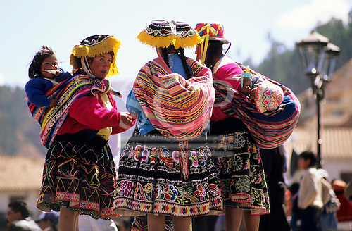 Cusco, Peru. Women in colourful traditional costume carrying their babies slung on their backs.
