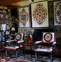 A pair of upholstered wooden armchairs stand infront of the fireplace in the library  decorated with leaf collages