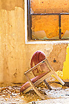A broken chair lays on the floor in an old, desserted building in an urban area.