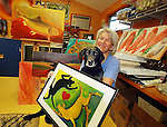 "PARTNERS IN ART--South Carroll artist Melinda Byrd is known for her whimsical images.of fish and dogs.  Melinda draws some of her inspiration from.her ""Lab Assistant"", ""Hooper""--a black lab who is also a fine lap dog."