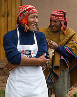 Peru, Urubamba Valley, Quechua Village of Misminay.  Two Men Talking.  The one wearing the apron is a chef.