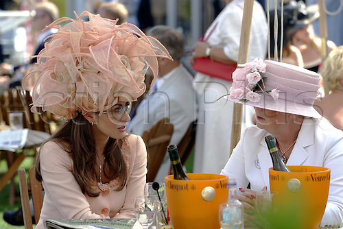28 July 2004: Racegoers enjoying a glass of champagne at Goodwood Photo: Glyn Kirk/Action Plus...horse racing 040728 flat dress hat hats fashion
