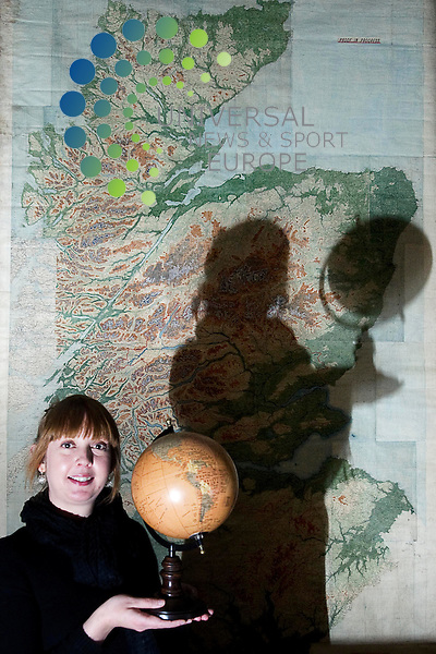 The Firm that put Scotland on the Map, exhibition opens on 7th December at the National Library of Scotland give an opportunity to learn about the Scots who mapped the world and celebrates the Edinburgh based firm of John Bartholomew and Son who was one of the finest publishers of maps in the world. Edinburgh, Scotland, 6th December, 2012. Pictured Karla Baker, Bartholomew Archive Curator with a globe showing a partly discovered world and the largest map in the collection, of Scotland showing orographical features. .Picture:Scott Taylor Universal News And Sport (Europe) .All pictures must be credited to www.universalnewsandsport.com. (Office)0844 884 51 22.