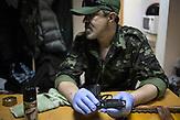 """Ruslan, Aktivist aus der Türkei, seit 10 Jahren in der Ukraine, bei diversen Gruppierungen, jetzt beim Sektor, er unterstützt den """"nationalen Kampf"""", Mitglieder des Pravyj Sektor im besetzten Postgebäude in Kiew / Members of the Prawy Sektor in an occupied postoffice."""