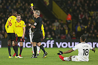 Referee Martin Atkinson (C) shows a yellow card to Abdoulaye Doucoure (L) of Watford for his foul against Jordan Ayew (R) of Swansea City during the Premier League match between Watford and Swansea City at the Vicarage Road, Watford, England, UK. Saturday 30 December 2017