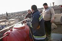 Feuerwehr in Qamishli, Rojava/Syrien.<br /> Von sieben Feuerwehr-Fahrzeugen die der YPG-Regierung in Qamishli zur Verfuegung stehen, ist nur eines funktionstuechtigt. Fuenf Fahrzeuge sind mit vorhandenen Mitteln nicht zu reparieren - Motorschaden, unbenutzbare Fahrerkabinen, defekte Stromleitungen.<br /> Zusaetzlich zumden Augaben der Feuerwehr muessen die 12 Feuerwehrmaenner - je 3 von ihnen arbeiten in 24-Stundenschichten - auch noch Wasser in Stadtteile ohne Wasserversorgung verteilen (im Bild).<br /> 15.12.2014, Qamishli/Rojava/Syrien<br /> Copyright: Christian-Ditsch.de<br /> [Inhaltsveraendernde Manipulation des Fotos nur nach ausdruecklicher Genehmigung des Fotografen. Vereinbarungen ueber Abtretung von Persoenlichkeitsrechten/Model Release der abgebildeten Person/Personen liegen nicht vor. NO MODEL RELEASE! Nur fuer Redaktionelle Zwecke. Don't publish without copyright Christian-Ditsch.de, Veroeffentlichung nur mit Fotografennennung, sowie gegen Honorar, MwSt. und Beleg. Konto: I N G - D i B a, IBAN DE58500105175400192269, BIC INGDDEFFXXX, Kontakt: post@christian-ditsch.de<br /> Bei der Bearbeitung der Dateiinformationen darf die Urheberkennzeichnung in den EXIF- und  IPTC-Daten nicht entfernt werden, diese sind in digitalen Medien nach &sect;95c UrhG rechtlich geschuetzt. Der Urhebervermerk wird gemaess &sect;13 UrhG verlangt.]