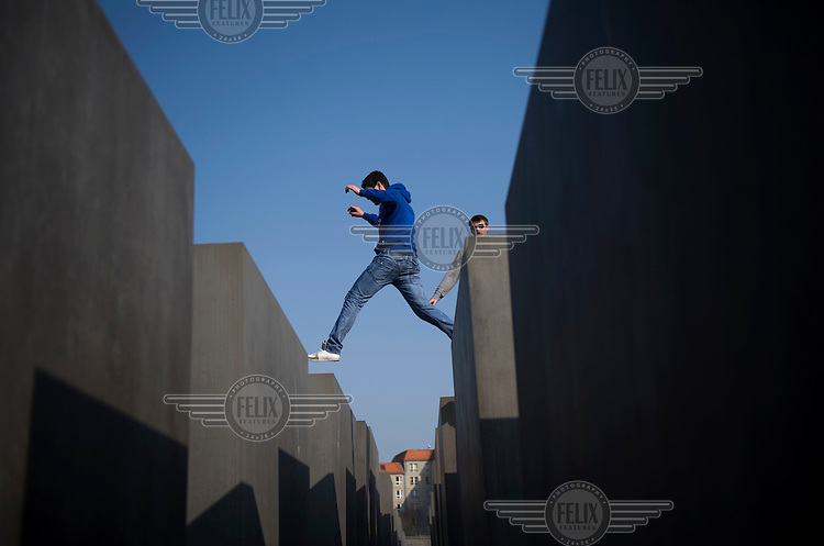 A young man jumps from one pillar to another at the Holocaust memorial designed by architect Peter Eisenman in Berlin. .