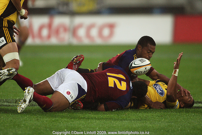 Hurricanes winger David Smith collects his lost ball in the tackle of Alando Soakai and Johnny Leota during the Super 14 rugby union match between the Hurricanes and Highlanders at Westpac Stadium, Wellington, New Zealand on Friday 20 February 2009. Photo: Dave Lintott / lintottphoto.co.nz