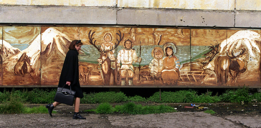 039078.AA.0820.warming31.kc--Bering Sea, Off Providenya, Russia--A woman walks past a mural depicting the Eskimo heritage of the Russian people. The story deals with the enviromental issue of global warming throughout the region of Russia directly across the Bering Sea from Nome, Alaska. The story touches on the people, their way of living, the rough economy and the extent they are effected by the slowly warming temperature as documented by scientists.  More Details To Come.