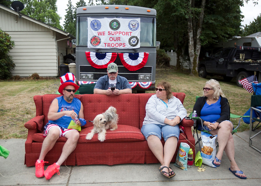 Tony Benson (L)  wears a patriotic hat as he watches the Fourth of July Parade with his dog Dallas, and others in Ridgefield Monday July 4, 2016. (Photo by Natalie Behring/ for the The Columbian)