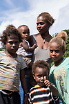 Russell Islands, Solomon Islands; a local mother and her children standing on the back deck of a liveaboard dive boat, while visiting to deliver fresh fruits and vegetables in their canoe