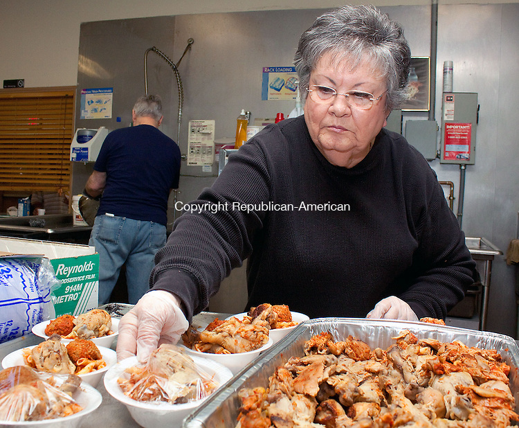 WATERBURY CT-APRIL 11 NEW_0114DA10- Beverly Diaspro of Southbury volunteers preparing lunch as her husband Joe washes  dishes behind her at St. Vincent De Paul Mission in Waterbury Soup Kitchen on Thursday. The Soup Kitchen offers hot, full-course noon meals to the poor and homeless. The mission of the Soup Kitchen is to provide decent meals to the hungry, who are not capable of providing for themselves..Darlene Douty Republican American