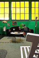 Yellow light bounces off window awnings intensifying the vibrant green interior of the living room, crammed with 20th century treasures
