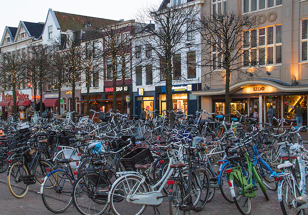 Dutch bicycles in the town square at night, Leiden, Netherlands.