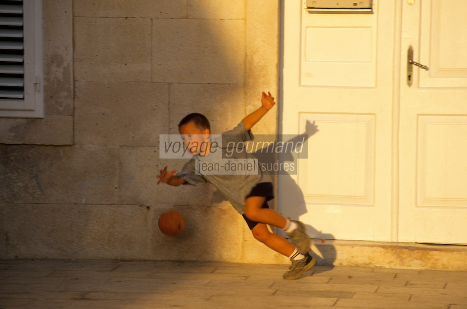 Europe/Croatie/Dalmatie/ Ile de Vis/Vis:  Enfant jouant au football sur le port