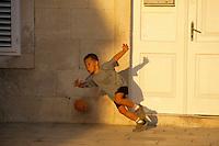 Europe/Croatie/Dalmatie/ Ile de Vis/Vis:  Enfant jouant au football sur le port
