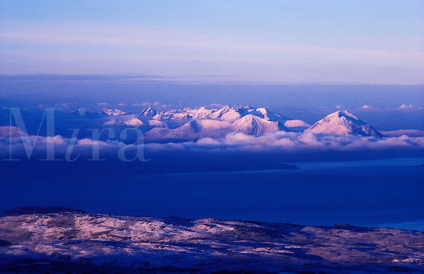 Scotland.  Isle of Skye from Applecross, with the Cuillin Hills breaking through the early morning cloud.