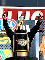 Nov 10, 2013; Pomona, CA, USA; NHRA funny car driver John Force is blocked by the championship trophy during the Auto Club Finals at Auto Club Raceway at Pomona. Mandatory Credit: Mark J. Rebilas-