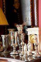 A collection of mercury glass, also known as silvered glass, vases, statues of the Virgin Mary and an English clock are displayed on a chest of drawers