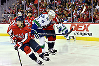 WASHINGTON, DC - FEBRUARY 05: Vancouver Canucks center Elias Pettersson (40) slips between Washington Capitals center Lars Eller (20) and Capitals defenseman Dmitry Orlov (9) during the Vancouver Canucks vs. the Washington Capitals NHL game at Capital One Arena in Washington, D.C.. (Photo by Randy Litzinger/Icon Sportswire)