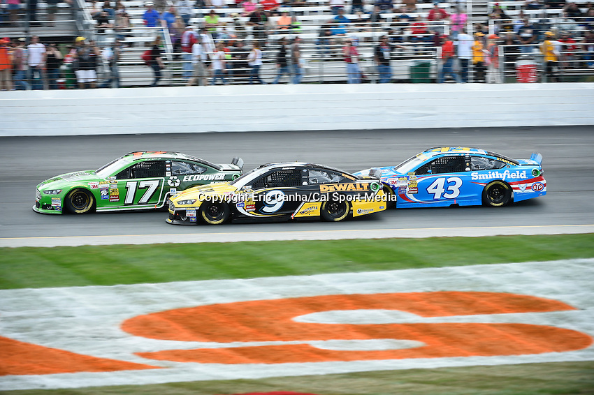 September 21, 2014 - Loudon, New Hampshire, U.S. - Sprint Cup Series driver Marcos Ambrose (9) works the inside lane against Ricky Stenhouse Jr. (17) and Aric Almirola (43) at the Nascar Sprint Cup Series Sylvania 300 race held at the New Hampshire Motor Speedway in Loudon, New Hampshire.   Eric Canha/CSM