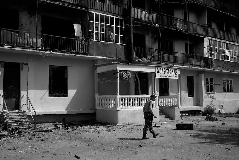 "Gori, Georgia, August 20, 2008.A Russian army ""irregular"" prowls alone in the destroyed buildings, a potentially dangerous situation for the few inhabitants still in the area.The Russian aviation and artillery has badly damaged a group of appartment buildings at the edge of the city next to a georgian Army base. Very poor to begin with, many inhabitants have lost everything they had.."