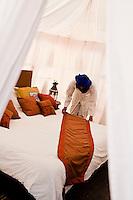 A room attendant preparing a bedroom in the tented camp of Ubari Magic Lodge