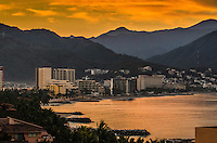 Fine Art Landscape Photograph, of a golden sunrise depicting the city skyline of Puerto Vallarta, Mexico. The background of this city skyline is framed by the mountains and golden clouds. The foreground of this skyline is framed by the golden textures of the shimmering ocean ripples that are revealed by the strong side lighting of the rising sun.
