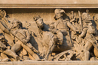 Arc de Triomphe, Paris.  Details of sculpture of Napoleon on horseback leading his troops in battle.  Visible details include soldiers' uniforms, weapons, stirrups, medals.  Shot at sunrise.  July 2008
