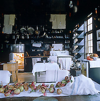 The open-plan kitchen-diner seen from over the dining room table which is strewn with fallen apples
