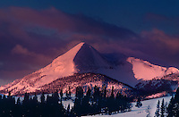 798600013 winter sunrise paints snow covered antler peak in pink alpenglow as storm clouds clear over yellowstone national park in wyoming