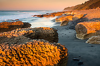 Sunset on rocky beach with limestone formations at Paturau on west coast of South Island, Nelson Region, New Zealand, NZ