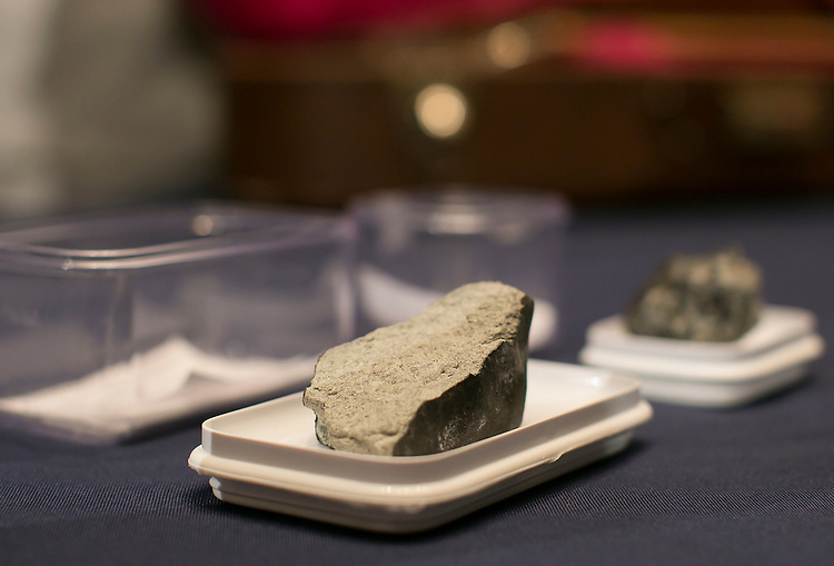 "UNITED STATES - JUNE 17 - A piece of the Lorton Virginia Meteorite, which fell in Lorton, Virginia, on Monday, January 18, 2010, is seen on display from the National Museum of Natural History, before a House Administration Committee Hearing on ""The State of the Smithsonian"" in the Longworth House Office Building on Wednesday, June 17, 2015. In the background is a piece of the meteorite that fell in Chelyabinsk, Russia, on February 15, 2013. Both meteorites are ordinary chondrites, which come from the atria belt between Mars and Jupiter.  (Photo By Al Drago/CQ Roll Call)"