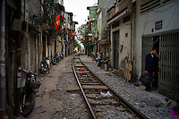A man stops in a doorway in a neighborhood built along railroad tracks in Hanoi, VIetnam on 18 February 2010.