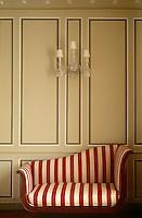 In this living room a crystal wall sconce hangs above a red and white striped Empire sofa