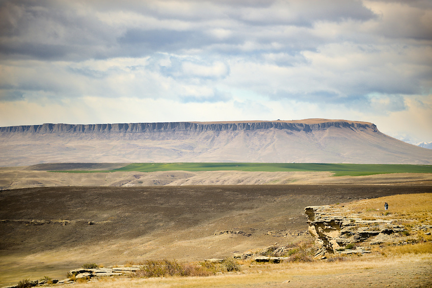 Visitors explore the rim of the buffalo jump at First Peoples Buffalo Jump State Park near Ulm,  Montana. Square Butte is seen rising in the distance.