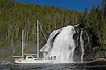 Island Odyssey  approchant une belle cascade. Le bateau est le seul moyen de  saventurer dans le dédale de fjords de la foret pluviale temperee qui s etend sur 400 km de long entre Prince Ruppert et le nord de lile de Vancouver..Island Odyssey ketch  nearby a big waterfall