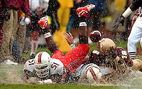 Florida State quarterback #16 Chris Weinke loses the football after being hit by Miami Hurricanes linebacker #51 Jonathan Vilma during the 'Canes 22-14 victory over Florida State Seminoles in Tallahassee, Florida. (Rick Wilson/The Florida Times-Union)