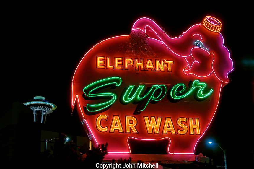 Rotating Elephant Super Car Wash neon sign at night with Space Needle in back in downtown Seattle, Washington state, USA