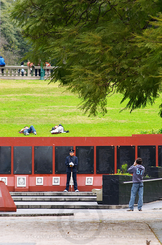 Monument commemorating the Falkland war Islas Malvinas on the Plaza San Martin Square, black marble plaques with names engraved of the soldiers in the war on red stone background, map of the island, two military honour guards in a park. a man taking a photo of the guard, young people sleeping on the grass behind. the Plaza San Martin Square renamed Plaza de la Fuerza Aerea or Plaza Fuerza Retiro Buenos Aires Argentina, South America