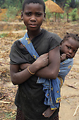 Lukulu Game Management Area, Zambia. Young girl with a baby girl on her back.