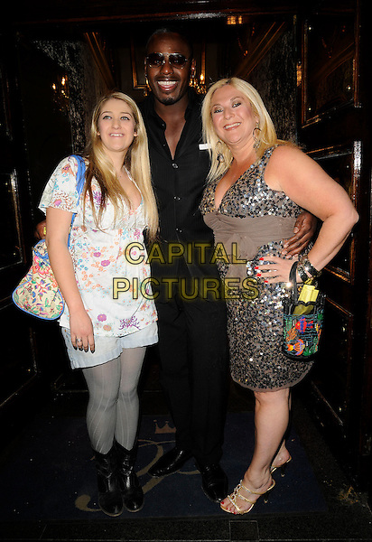 DAUGHTER, VANESSA FELTZ & BEN OFOEDU.Miss Great Britain 2009 Grand Final,  Cafe de Paris, London, England. .May 12th, 2009 .full length black suit beige silver sequins sequined sash waist white top boots dress tights mother mom couple hand on hip .CAP/CAN.©Can Nguyen/Capital Pictures.