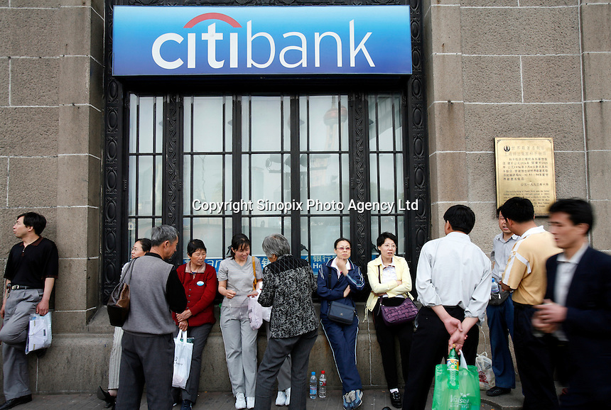 Pedestrians take a break outside of a Citibank branch in Shanghai, China..