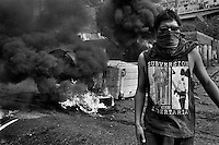 A Chilean student, having his face covered by a scraf, stands in front of the burning barricade during the anti-government protest in Valparaíso, Chile, 21 May 2002.