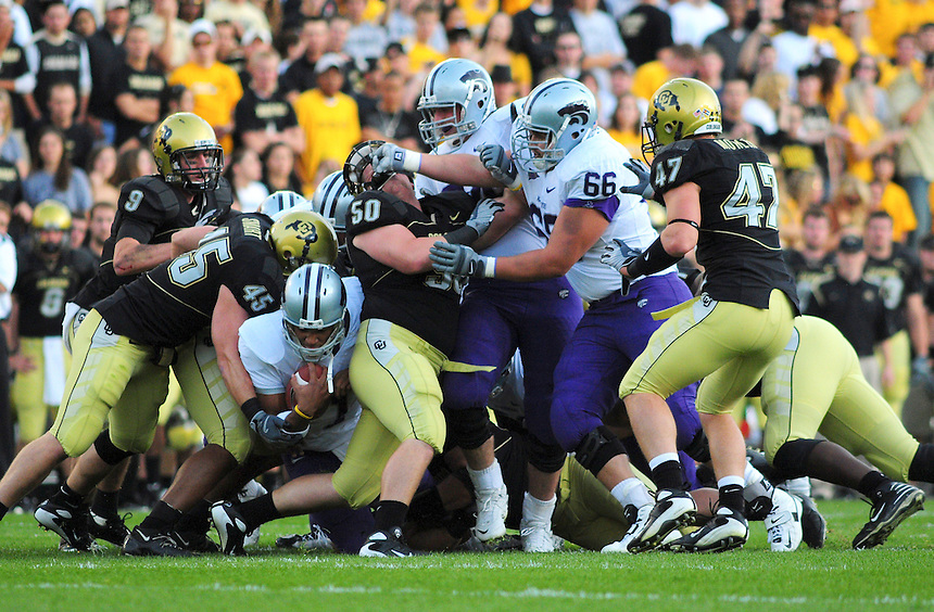 18 October 08: Kansas State quarterback Josh Freeman (at left with ball) looks for a hole through the Colorado defense. Tackling Freeman is Colorado linebacker Jeff Smart (45). Blocking for Freeman is guard Eric Benoit (66) who has his hands in the face of Colorado tackle Curtis Cunningham. Also on the play is Colorado linebacker Shaun Mohler (47). The Colorado Buffaloes defeated the Kansas State Wildcats 14-13 at Folsom Field in Boulder, Colorado.