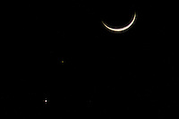 The crescent moon and Venus shine on either side of the faint red glow of Mars.