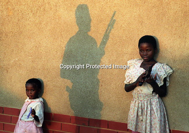 A military man protects children at a church on April 21, 1994 in Lindelani, South Africa. Their families are ANC supporters and they fled from violent clashes with the IFP (Inkatha freedom party) days before the first democratic election in South Africa on February 27, 1994. Nelson Mandela was voted in as the first democratically elected president in South Africa. He served one five-year term and retired in 1999.