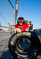 Jul 26, 2019; Sonoma, CA, USA; A young NHRA fan sits on a Goodyear tire during qualifying for the Sonoma Nationals at Sonoma Raceway. Mandatory Credit: Mark J. Rebilas-USA TODAY Sports