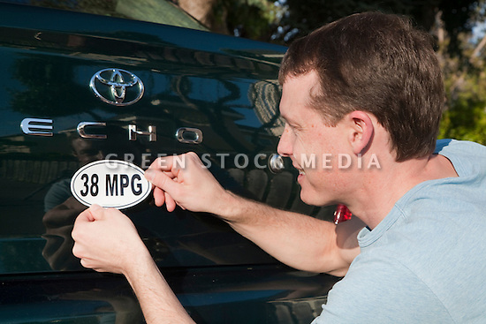 Mid adult man placing a 38 miles per gallon fuel efficiency bumper sticker installed on Toyota Echo car. Sticker from MPG Stickers (mpgstickers.com), a grassroots, nonprofit campaign which aims to accelerate the adoption of fuel efficient vehicles in the United States. California, USA. Property released from mpgstickers.com.
